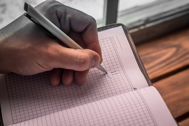 Close up view of men's left hand with pen drawing smile in notepad. personal organizer
