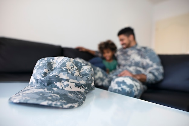 Close up view of military camouflage cap and off-duty soldier in uniform enjoying reunited happy family moments.