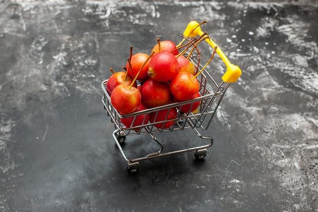 Vista ravvicinata del mini grafico della spesa con ciliegie rosse su grigio
