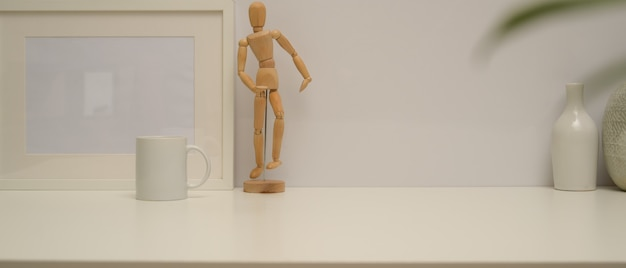 Close up view of minimal home interior design with copy space, frame, wooden figure, vases and mug on white desk