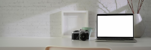 Close up view of minimal workspace with blank screen laptop, camera, decorations and copy space on white table