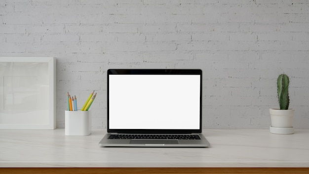 Close up view of minimal workspace with laptop on marble desk with white white wall