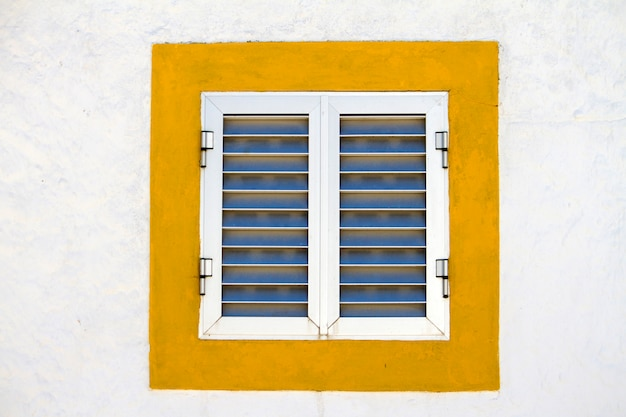 Close up view of a modern aluminum window with a yellow frame.