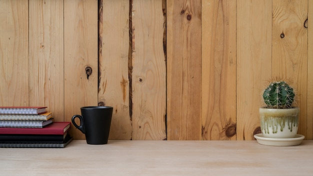 Close up view of modern rustic workspace with mug, notebooks, cactus pot