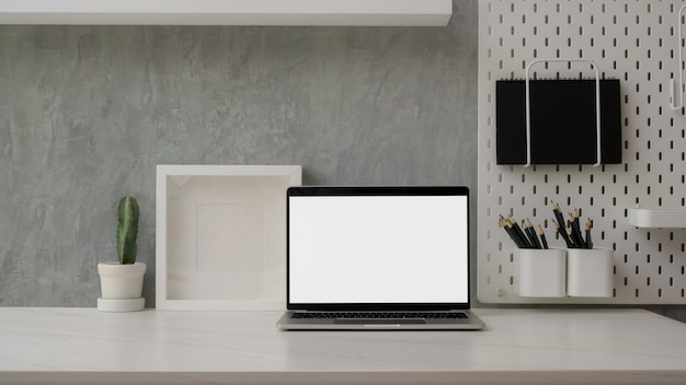 Close up view of modern workspace with blank screen laptop, decorations and copy space