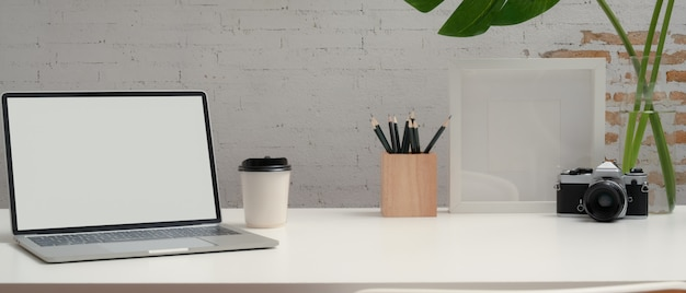 Close up view of modern workspace with mock up laptop, stationery, camera, decorations and copy space on white desk