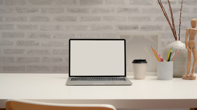 Close up view of modern workspace with mock up laptop, stationery, decorations and copy space on white desk with chair