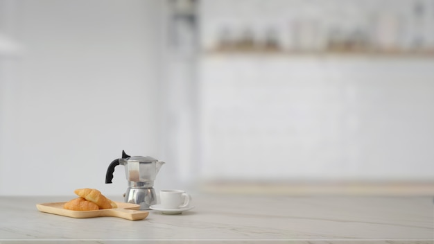 Close up view of moka pot, coffee cup, croissant and copy space on marble table with blurred kitchen room