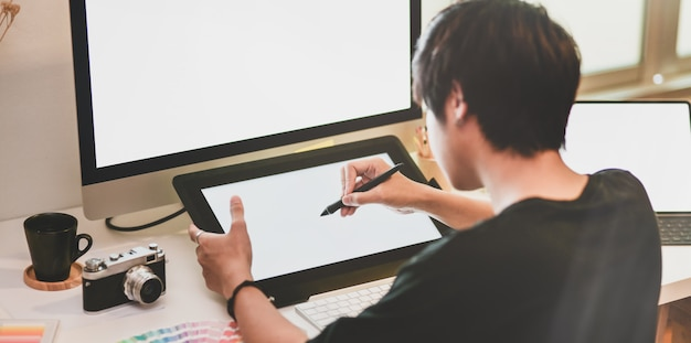 Close-up view of motivated photographer drawing on tablet