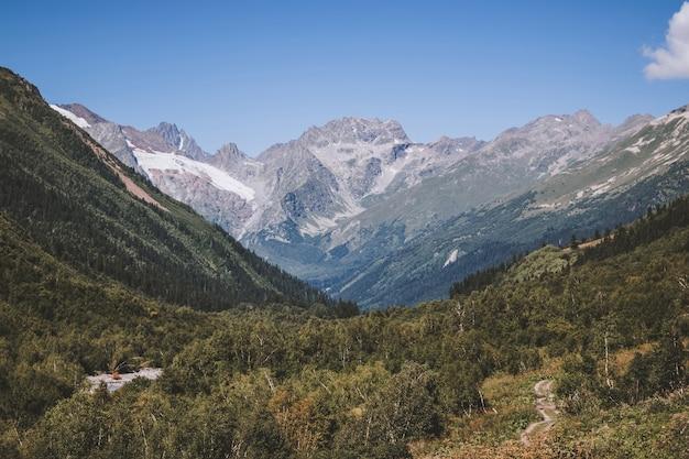 Крупным планом вид на горы и речные сцены в национальном парке домбай, кавказ, россия, европа. летний пейзаж, солнечная погода, драматическое голубое небо и солнечный день