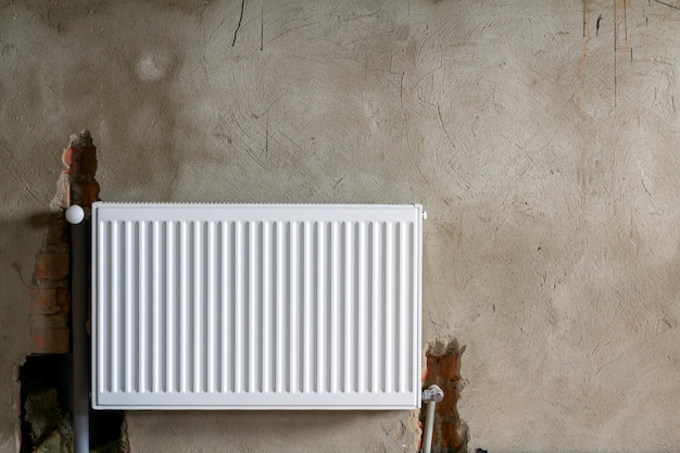 Close-up view of new isolated installed heating radiator on brick rough plastered wall in an empty room of a newly built apartment or house. construction, maintenance, plumbing and repairing concept.