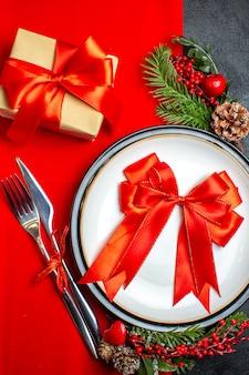 Vista ravvicinata del nuovo anno sfondo con nastro rosso sulla piastra della cena set di posate decorazione accessori rami di abete accanto a un regalo su un tovagliolo rosso