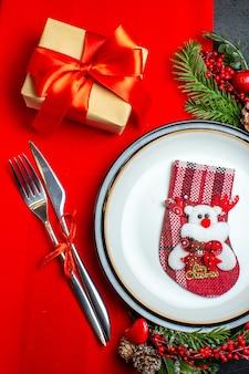Vista ravvicinata del nuovo anno sfondo con calzino di natale sulla piastra per la cena set di posate accessori per la decorazione rami di abete accanto a un regalo su un tovagliolo rosso