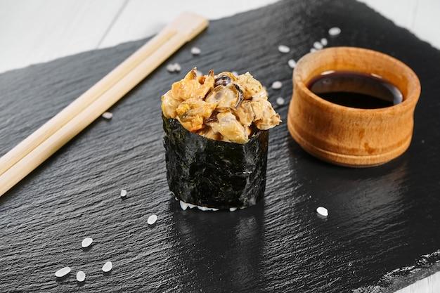 Close up view on nigiri sushi on slate plate isolated on white wooden background. japanese sushi food