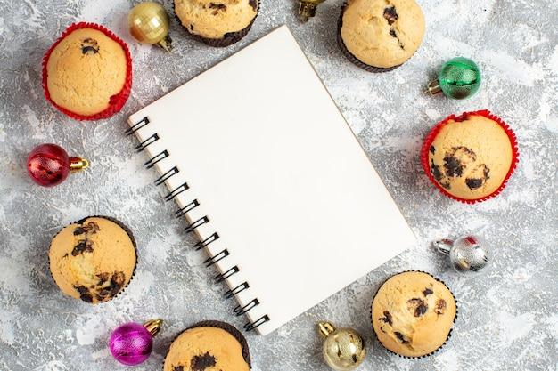 Vista ravvicinata del taccuino tra deliziosi piccoli cupcakes appena sfornati e accessori decorativi sul tavolo del ghiaccio
