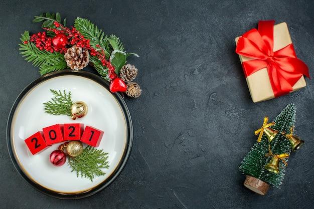 Vista ravvicinata di numeri decorazione accessori su un piatto rami di abete cono di conifera albero di natale su sfondo nero