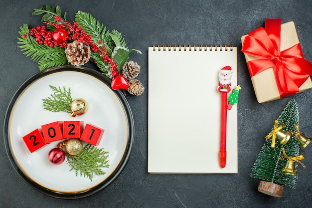 Close up view of numbers decoration accessories on a plate fir branches conifer cone christmas tree notebook with pen on dark background