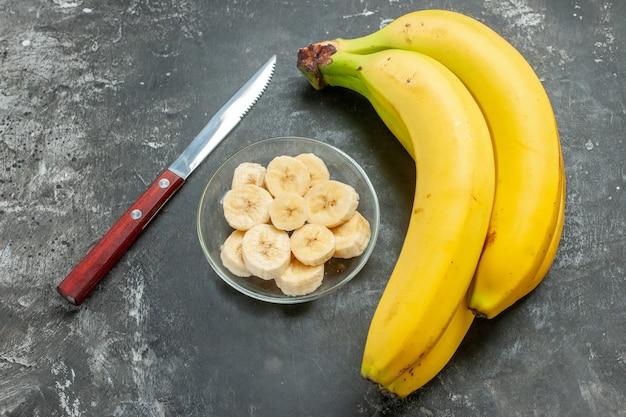 栄養源の新鮮なバナナの束をクローズアップし、灰色の背景にガラスの鍋でみじん切り