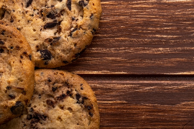 Close up view of oatmeal cookies with chocolate chips on wooden