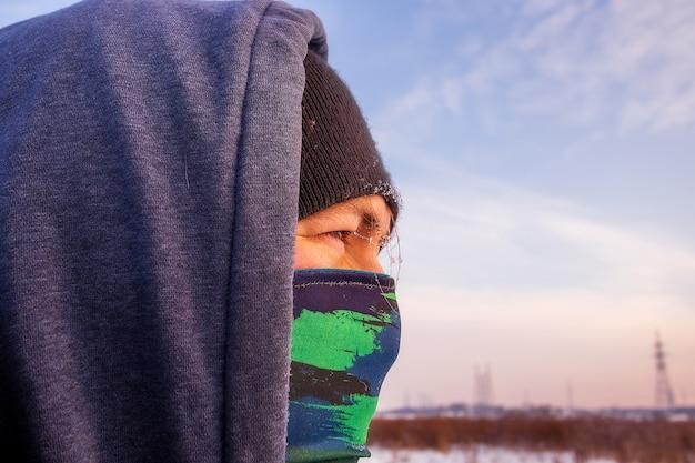 마스크와 후드 겨울 재킷으로 스카프 facewith 백인 남자의 보기를 닫습니다.