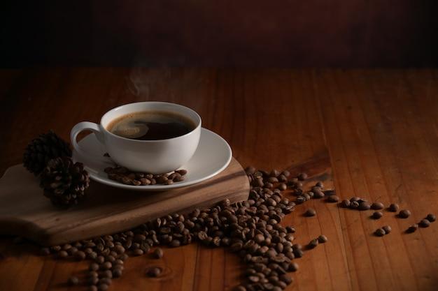 나무 테이블에 커피 콩으로 장식 된 나무 쟁반에 뜨거운 커피 한 잔의 뷰를 닫습니다
