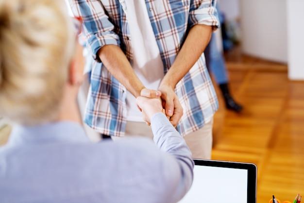 成功した取り決めの後の2人の若いビジネス人々のしっかりした握手のビューをクローズアップ。