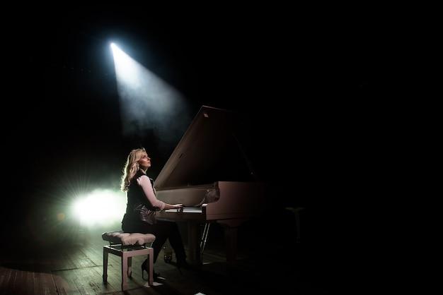 シーンのコンサートホールでピアノを弾く少女のクローズアップ表示