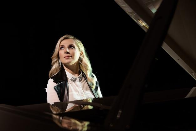 Крупным планом вид девушки играет на пианино в концертном зале на сцене
