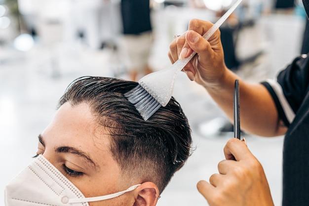 미용실의 의자에 마스크를 쓴 남자의 머리를 색칠하는 미용사의 클로즈업