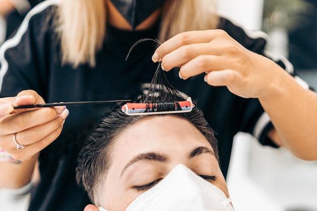 고객의 머리카락을 말리는 송곳이 있는 마스크로 고객의 머리카락을 분리하는 미용사의 클로즈업