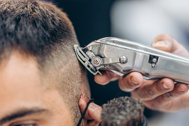 理髪店で白人の大人の顧客の髪を剃る機械のクローズアップビュー