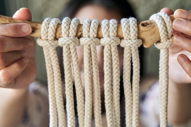 若い女性が手で作ったマクラメの装飾の拡大図