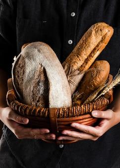 Взгляд конца-вверх человека держа корзину хлеба