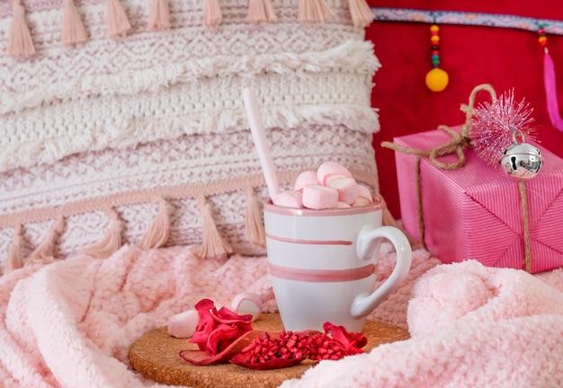 Крупным планом - розовый домашний уголок с подарочной упаковкой на одеяле, кружка с горячим какао с зефиром и рождественские украшения. праздники и концепция счастливых людей