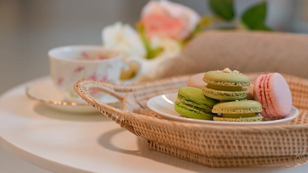 고리 버들 쟁반에 프랑스 다채로운 마카롱 접시와 커피 테이블에 차 컵의 뷰를 닫습니다