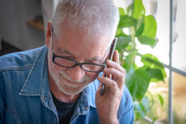 Крупным планом старший взрослый мужчина с белыми волосами и бородой с помощью мобильного телефона - интенсивный свет из окна. человек в джинсовой рубашке.