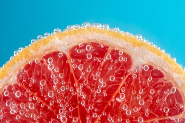 泡とソーダ水でグレープフルーツのスライスのビューを閉じます。