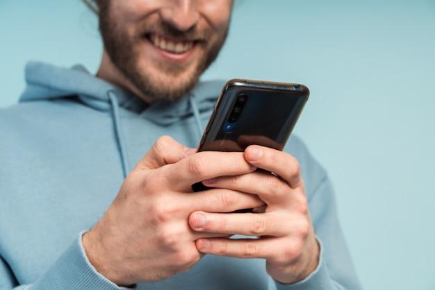 그의 손에 전화와 편안한 후드 티 셔츠에 수염을 가진 웃는 남자의 클로즈업보기.
