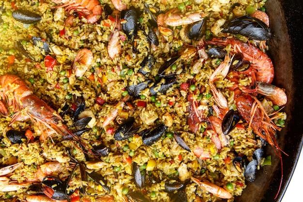 Крупным планом вид испанской паэльи из морепродуктов: мидии, королевские креветки, лангустин, пикша.