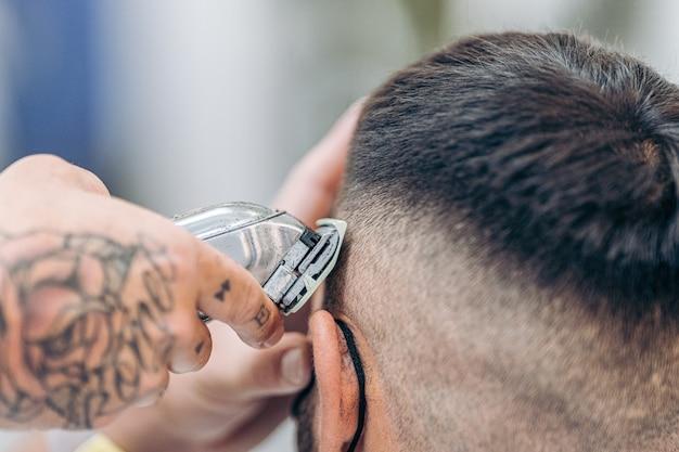 理髪店でコスチュームの髪を切るためにシェービングマシンを使用して入れ墨された手のビューをクローズアップ