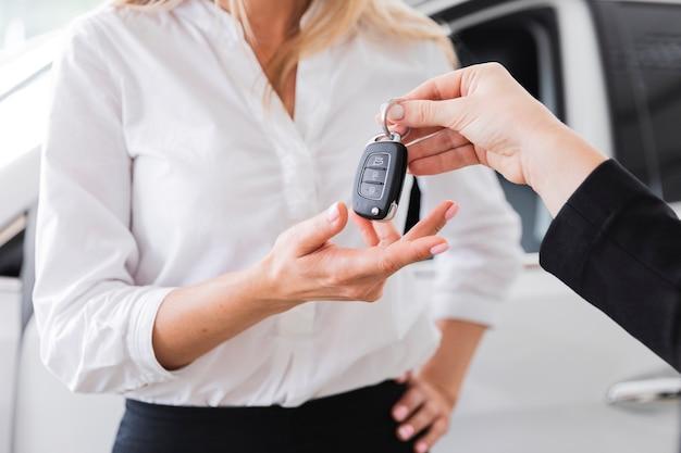 Взгляд конца-вверх женщины получая ключ автомобиля