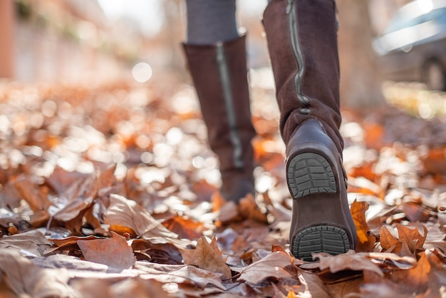 秋の通りの落ち葉を歩く女性のブーツのクローズアップビュー