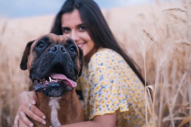 Крупным планом вид молодой счастливой женщины, обнимающей ее собаку в середине поля пшеницы. концепция природы и животных.