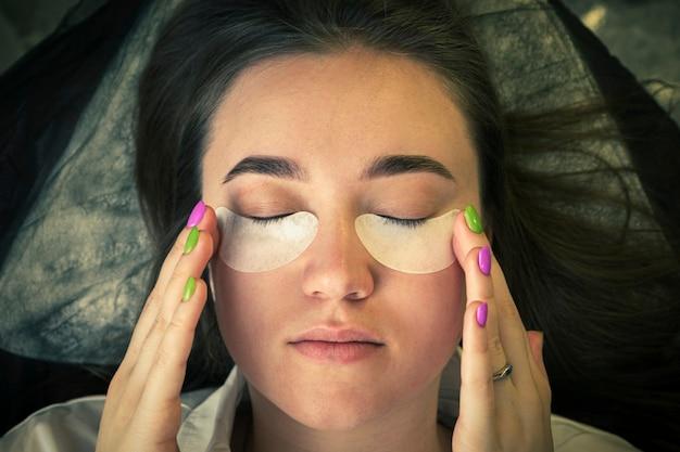 Крупным планом вид молодой женщины с пятнами под глазами от морщин и темных кругов. девушка сама делает косметическую процедуру. вид сверху