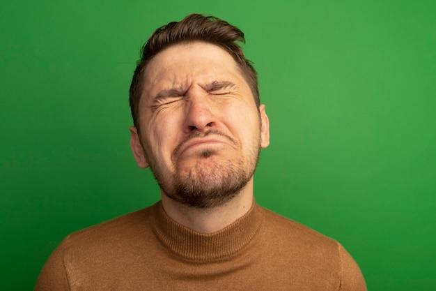 Крупным планом вид больного молодого белокурого красавца, закрывающего глаза, изолированного на зеленой стене