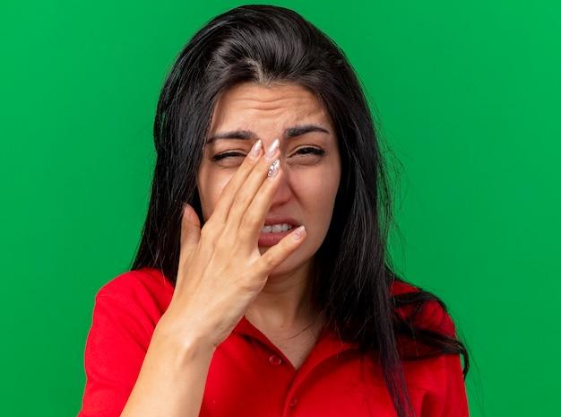 Крупным планом вид больной молодой кавказской больной девушки, касающейся носа, смотрящей в камеру, изолированную на зеленом фоне