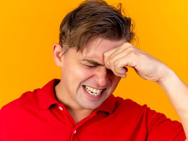 Крупным планом вид больного молодого красивого светловолосого больного человека, касающегося лба, страдающего от головной боли, с закрытыми глазами, изолированного на оранжевой стене