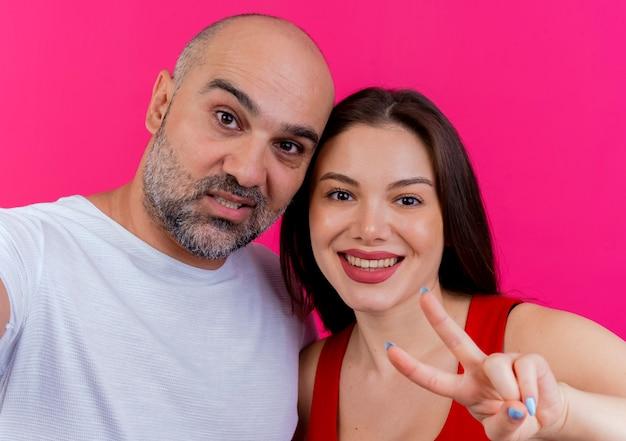 Крупным планом взрослая пара уверенный в себе мужчина и улыбающаяся женщина делают знак мира, оба выглядят