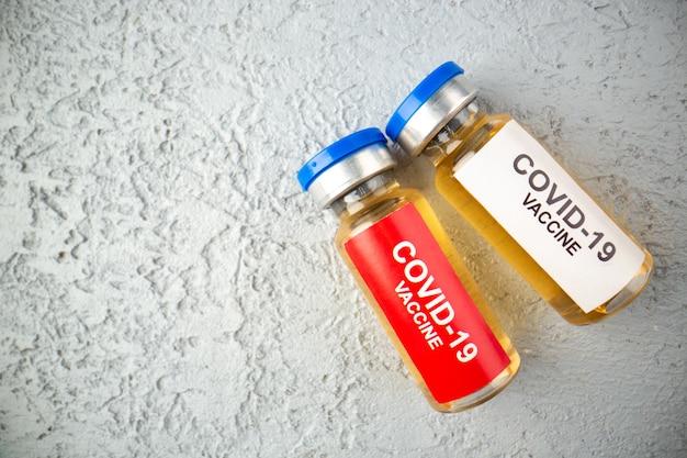 여유 공간이 있는 회색 모래 배경의 왼쪽에 covid-백신이 있는 앰플의 클로즈업 보기