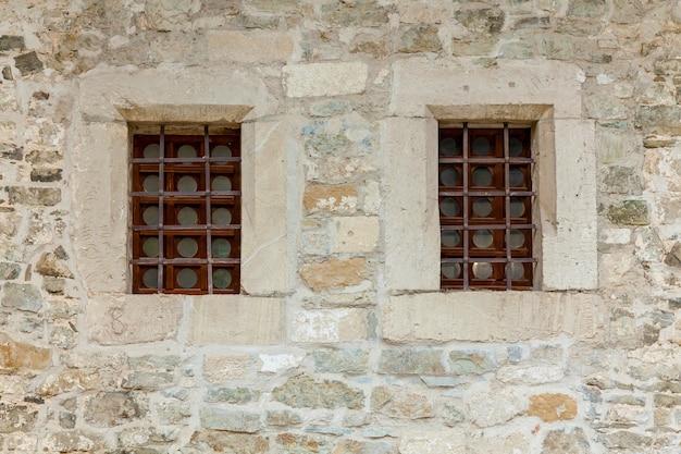 2つの大きな窓がある古代の建物の拡大図。廃屋のヴィンテージな外観。